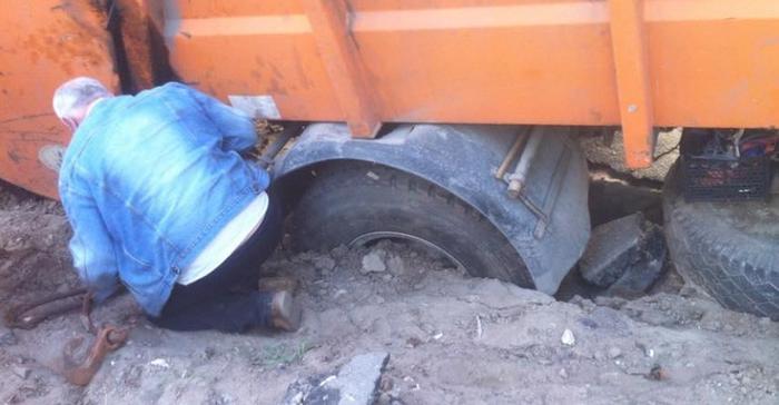 Асфальт устал: в Киеве под землю провалился мусоровоз