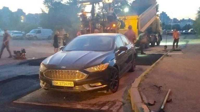 На Позняках в Киеве коммунальщики положили новый асфальт вокруг припаркованной машины